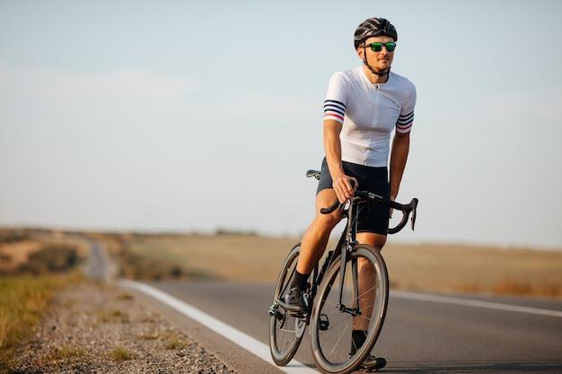 스포츠 의류, 검은 헬멧 및 시골에서 자전거를 들고 보호 안경에 강한 젊은 운동 선수