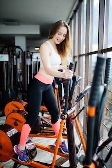 強い若い美しい女性は、楕円体でジムに従事しています。