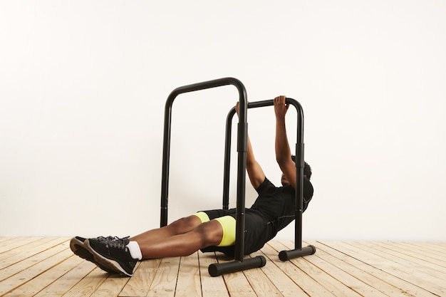 Strong young black male wearing black sports clothing with neon yellow half tights at the starting position for bodyweight rows on black mobile bars set on light wooden floor against white wall.