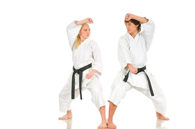 強い若いブロンドの女の子と無礼な空手男は、白い背景の上の着物のトレーニングに従事しています