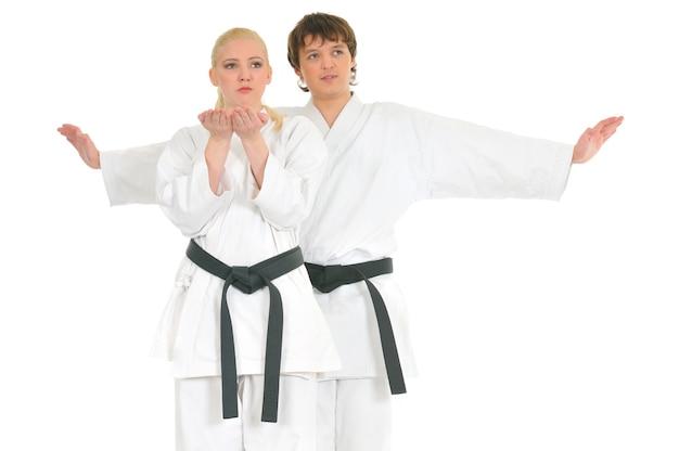 強い若いブロンドの女の子と無礼な空手男は白い着物のトレーニングに従事しています