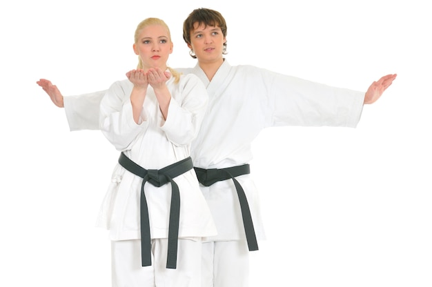 Strong young blonde girl and the impudent karate guy are engaged in training in a kimono on a white