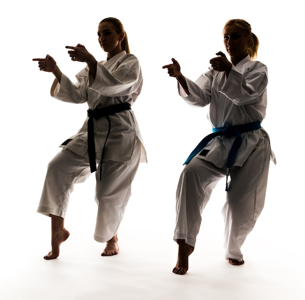 Strong young blonde girls are engaged in training in a kimono on a white background. young couple of professional athletes.
