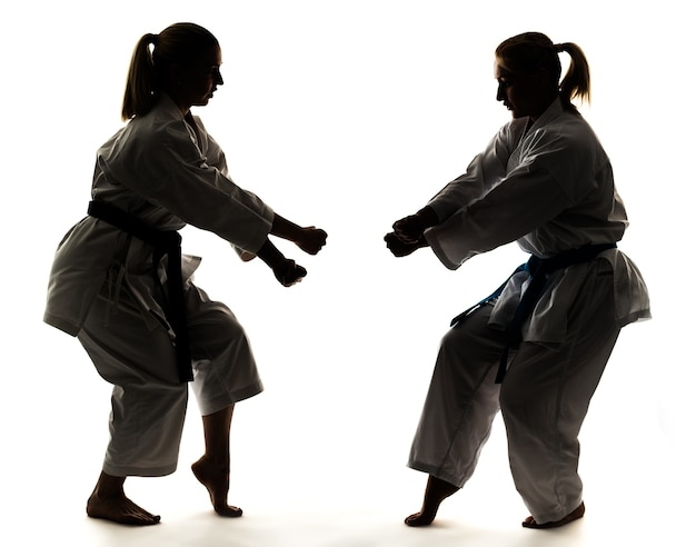 Strong young blonde girls are engaged in training in a kimono on a white background.