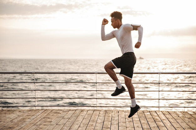 Strong young curly dark-skinned man in black sport shorts and long-sleeved t-shirt jumps and runs outside near sea