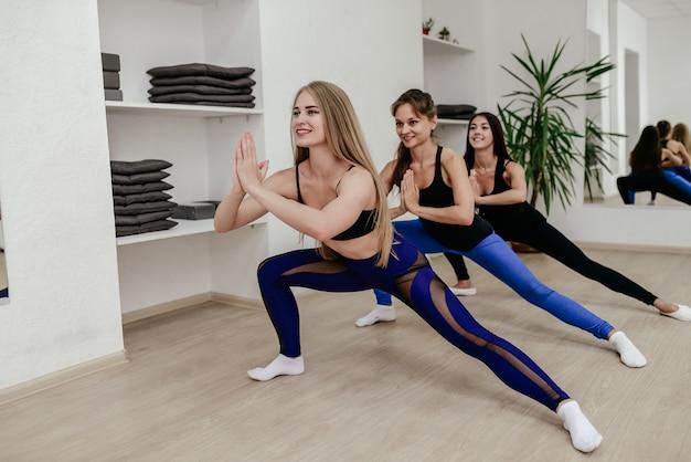 Сильные молодые женщины, осуществляющих в тренажерном зале. женщины делают штамповки тренировки в фитнес-клубе.