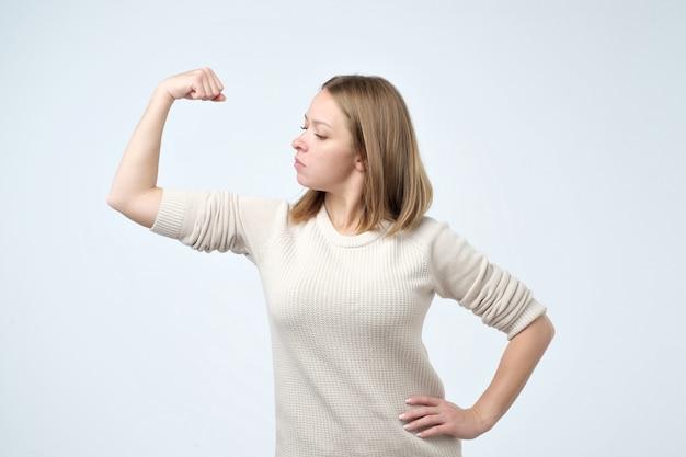 上腕二頭筋が自信があることを示す強い少女