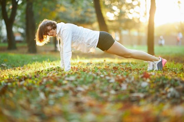 Сильная девушка делает упражнения на доске в солнечном парке