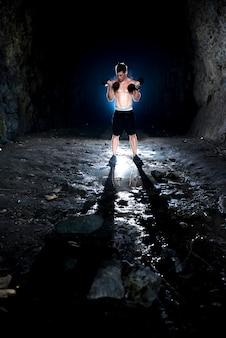 Сильный молодой мужчина, поднимающий гантели в пещере