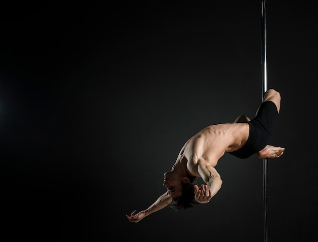 Strong young male performing a pole dance
