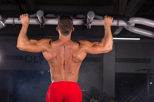 ジムの鉄棒で懸垂運動をしている強い青年。スポーツ、フィットネス、体操のトレーニング。