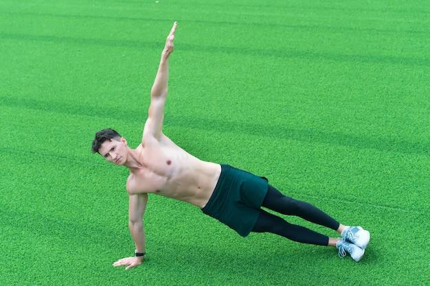 야외에서 스포츠를 하는 강한 청년. 잔디에 요가 연습 하는 남자. 피트니스 체육관에서 운동. 도시에서 요가를 하세요. 사이드 앵글 포즈. 체중 유연성 운동을 통한 근력 트레이닝 코어 바디.
