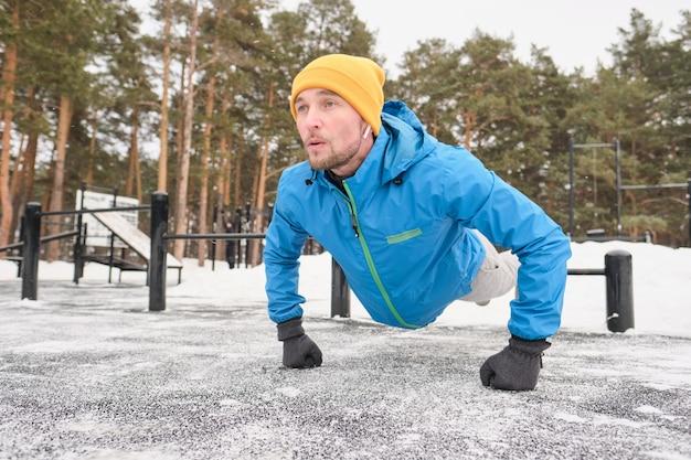 冬のトレーニングエリアでトレーニング中に地面から自分自身を押すイヤフォンの強い若い男