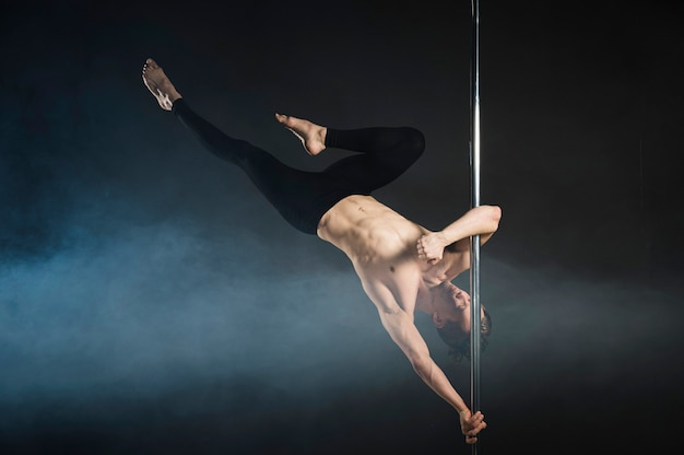 Strong young man performing a pole dance