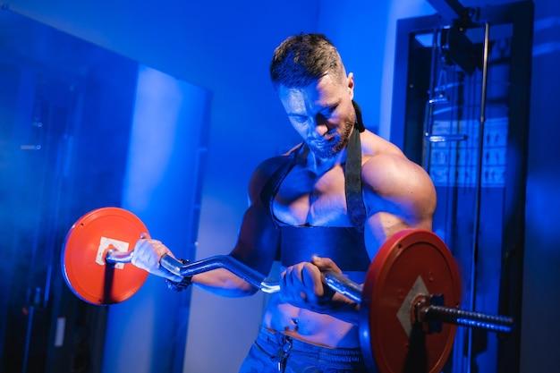 バーベルでエクササイズをしている美しい運動体を持つ強い青年。フィットネス、ボディービル。健康管理。
