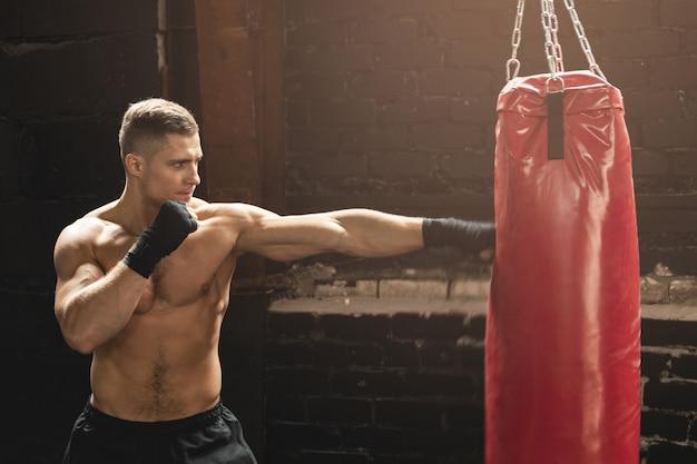 Сильный молодой боец мма и красная боксерская груша