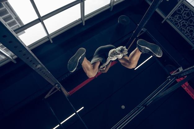 強い。若い筋肉質の白人アスリートがジムでトレーニングし、筋力トレーニングを行い、練習し、上半身に働きかけ、ロープを登ります。フィットネス、ウェルネス、スポーツ、健康的なライフスタイルのコンセプト。