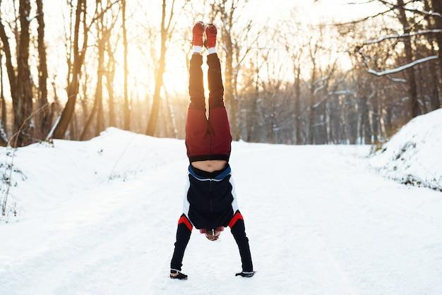 Сильный молодой бегун в спортивной одежде с наушниками делает стойку на снегу