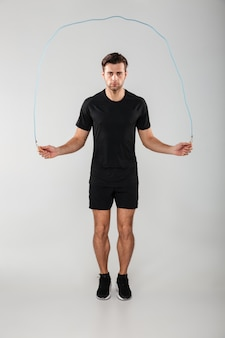 Strong young sports man jumping with skipping rope