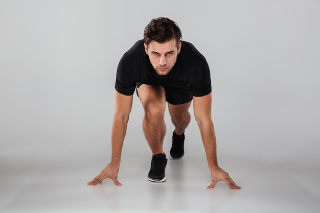 Strong young sports man runner isolated