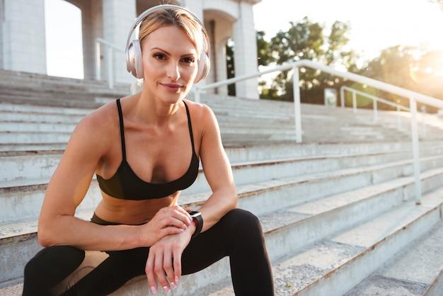 Сильная молодая спортивная женщина слушает музыку и использует часы