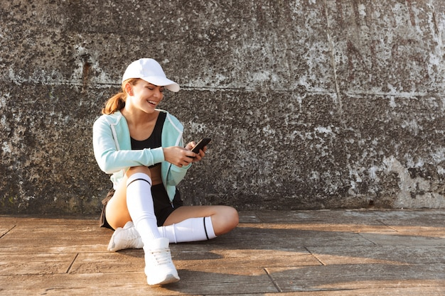 Strong young sports woman outdoors using mobile phone
