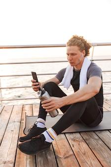 携帯電話を使ったイヤホンを持った屋外の強い若いスポーツマン。