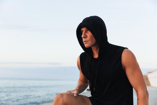 ビーチで屋外に立っている強い若いスポーツマン。