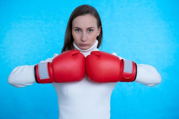 ボクシンググローブを身に着けている青い壁の壁の上に孤立してポーズをとる強い若い女性ボクサー。