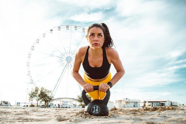 Strong young woman doing push-ups exercise at the beach Premium Photo