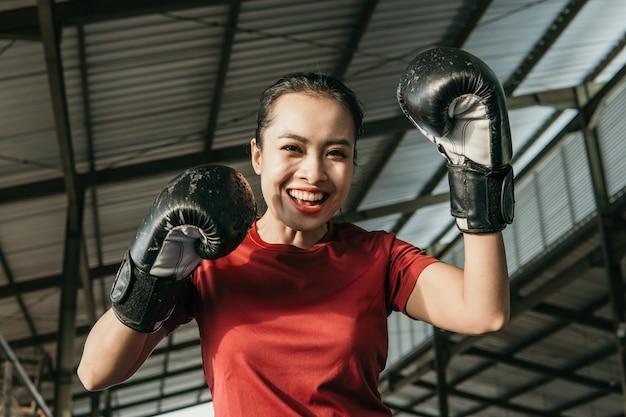 권투 장비에 강한 젊은 여자는 권투 훈련장에서 타격 동작을