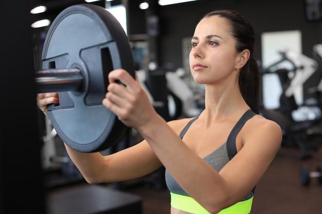 ジムでバーベルに体重を追加する美しい運動体を持つ強い若い女性。