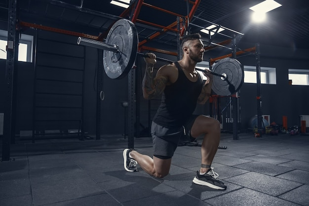 Stronger, young muscular caucasian athlete practicing lunges in gym with barbell. male model doing strength exercises, training his lower body. wellness, healthy lifestyle, bodybuilding concept.