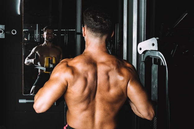 Strongman looking in the mirror while exercising in a gym