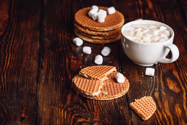マシュマロとワッフルスタックとホットチョコレートの白いカップと壊れたものとワッフルをストループ