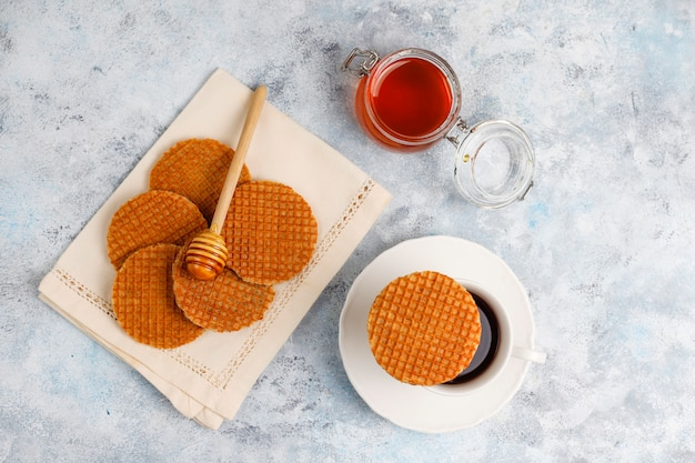 Stroopwafels, caramel dutch waffles with tea or coffee and honey on concrete