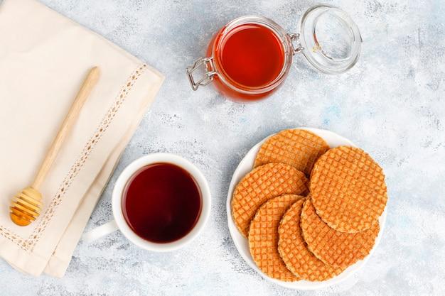 Stroopwafels、紅茶またはコーヒーと蜂蜜入りのキャラメルダッチワッフル