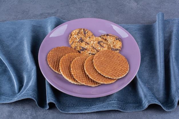돌 표면에 보라색 접시에 고립 된 stroopwafels