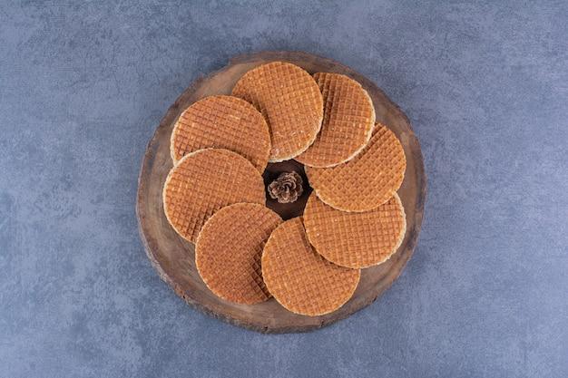 돌에 나무 접시에 고립 된 pinecone와 stroopwafels. 고품질 사진