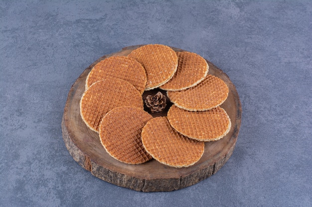 Stroopwafels with pinecone isolated in a wooden plate on a stone .high quality photo