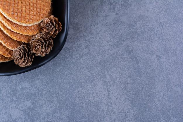 돌 표면에 검은 접시에 고립 된 pinecones와 stroopwafels