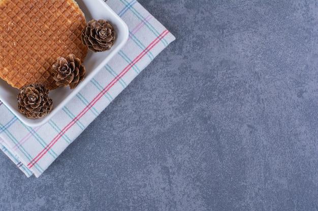 돌에 흰 접시에 고립 된 pinecones와 stroopwafels.