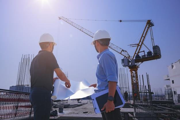 야외 건물 검사에 대해 논의하는 청사진이 있는 구조 엔지니어 및 감독