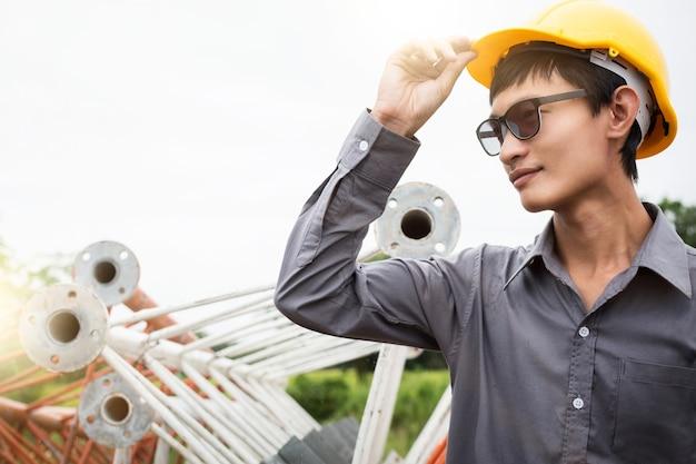 Инженер-строитель, стоящий перед стальным металлическим мостом на строительной площадке