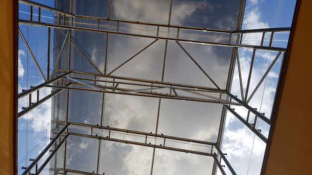Structural glazing of the facade. abstract background with glass ceiling elements in a modern building. view of the blue sky through a glass window, separated by lattice elements.