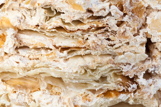 The structure of a cut cake with a layered structure with a cream of brown color, divided into pieces during the celebration of the wedding