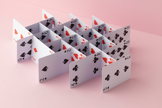 Structure made of cards on pink background