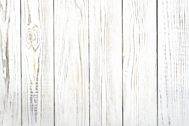 Structure of the old shabby boards of white color, located apeak, by close up  as a background.