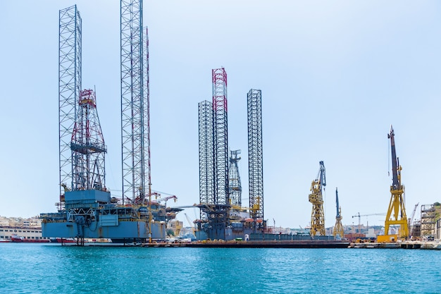 Structures with equipment for drilling oil wells is located in the sea near a shore of malta