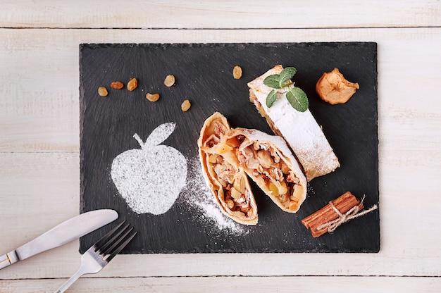 Штрудель с яблоками, изюмом и грецкими орехами в деревенском стиле на темном фоне
